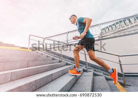 healthy lifestyle middle aged man runner running upstairs on cit