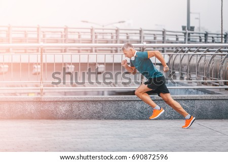 healthy lifestyle middle aged man runner running upstairs on city bridge road. Motion shot