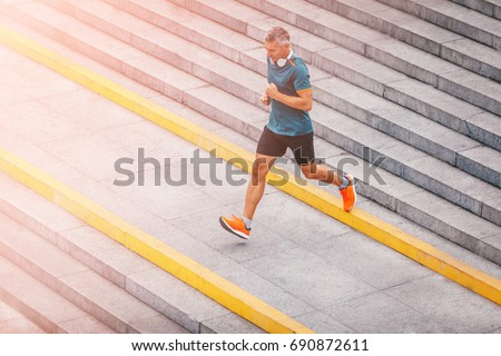 healthy lifestyle middle aged man runner running upstairs on city stairs. Motion shot.
