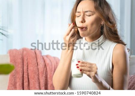 Healthy lifestyle. Portrait of beautiful smiling woman tasting fresh yogurt.