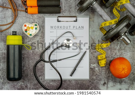 Healthy lifestyle powerlifting workout concept with grip cast iron olympic weight plates on a cement floor. Clip board with workout plan tab. Stock photo ©
