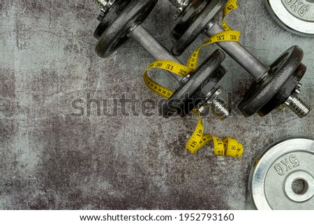 Healthy lifestyle powerlifting workout concept with grip cast iron olympic weight plates plates and tape measure on a cement floor. Empty copy space Stock photo ©
