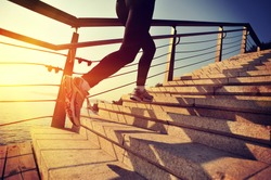 healthy lifestyle sports woman running up on stone stairs at sunrise seaside