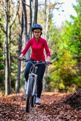 Healthy lifestyle - teenage girl biking in forest