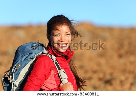 Healthy lifestyle woman hiker smiling happy outside on hiking trip. Beautiful natural candid smile on mixed race Caucasian / Asian female hiker outdoors in nature.
