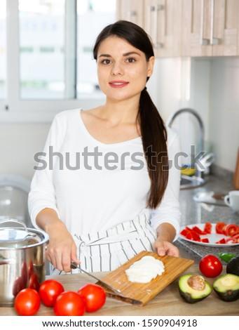 Healthy lifestyle, woman making fresh salad with mozzarella, avocado and tomato