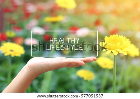 Healthy Lifestyle word on the white box. concept hand with natural background #577051537