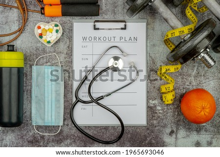 Healthy lifestyle workout concept with training equipment. The idea of how to achieve harmony and longevity while doing sports during Pandemic. Clip board with workout plan tab. Stock photo ©