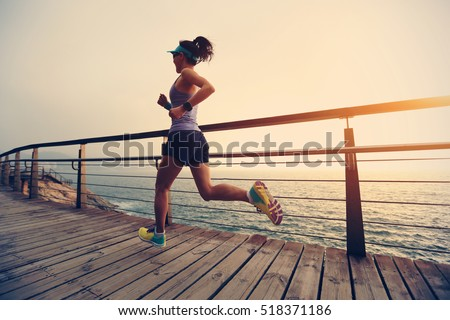 healthy lifestyle young fitness sports woman  trail runner running on seaside #518371186