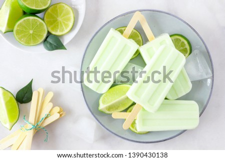 Healthy lime yogurt ice pops on a plate, top view table scene against a marble background