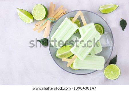 Healthy lime yogurt popsicles on a plate, top view against a marble background