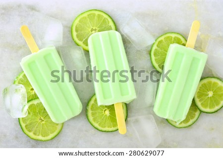 Healthy lime yogurt popsicles with fresh lime slices scattered on a white marble background