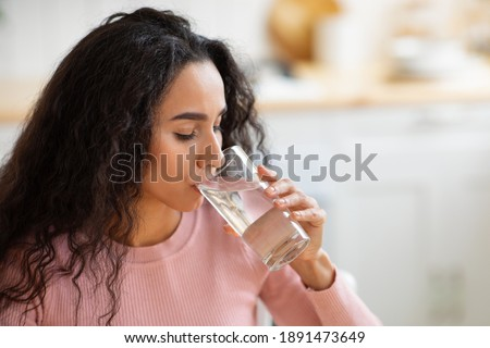 Healthy Liquid. Beautiful Brunette Woman Drinking Mineral Water From Glass In Kitchen, Thirsty Young Lady Enjoying Refreshing Drink At Home, Closeup Portrait With Selective Focus, Free Space