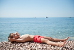 healthy little boy in red shorts lying on summer beach relaxing