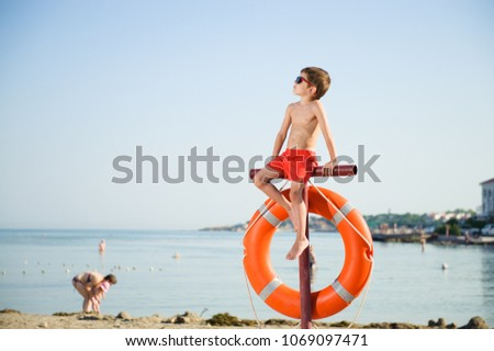 healthy little boy in sunglasses sits on pole with orange lifebuoy hanging on it on summer beach with people in baywatch Сток-фото ©