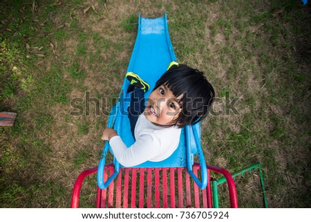 Healthy little kids are playing in the backyard, happy with the swings, rocking horses, slide carriages.