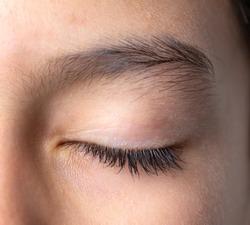 Healthy long eyelashes. Close-up of closed eye beautiful eyebrow and long eyelashes, natural look no make up