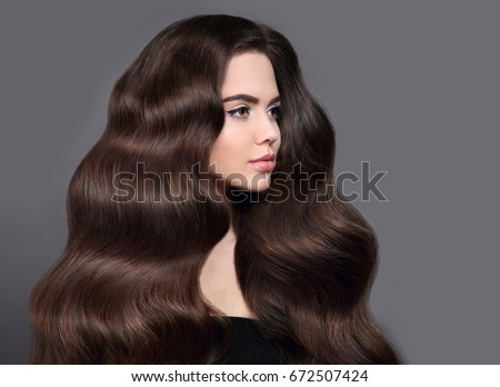 Healthy long wavy hair. Brunette girl beauty portrait with shiny brown hair. Beautiful model with hairstyle and makeup isolated on studio grey background. Shampoo care product. #672507424