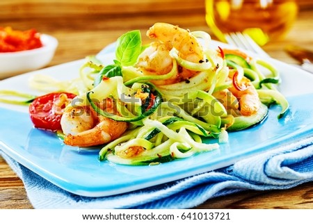 Healthy low carbohydrate seafood starter with a fresh raw vegetable salad and grilled spicy queen prawn tails dressed in olive oil served on a blue platter #641013721