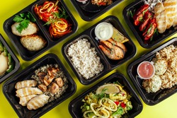 Healthy lunch at the workplace. Pick up food in black containers with Cutlery on a yellow background