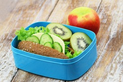 Healthy lunch box containing brown cheese sandwich, kiwi fruit and red apple on rustic wooden surface
