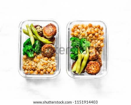 Healthy lunch box - spicy couscous with chickpeas, broccoli, green beans and turkey meatballs on dark background, top view. Copy space