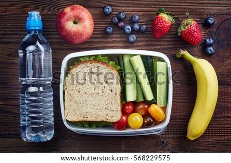 Healthy lunch box with sandwich and fresh vegetables, bottle of water and fruits on wooden background. From top view
