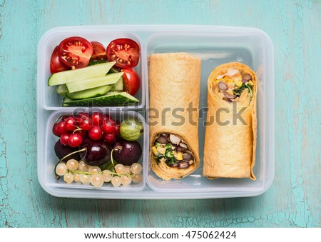 Healthy lunch box with tortilla wraps , fruits and vegetables, top view