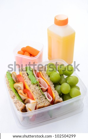 Healthy lunch box with turkey and ham sandwich with grapes, carrots and orange juice