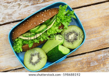 Healthy lunch box with wholegrain cheese roll, cucumber sticks and kiwi fruit