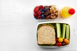 Healthy lunch boxes with sandwich, fresh vegetables, fruits and nuts on white wooden background. From top view