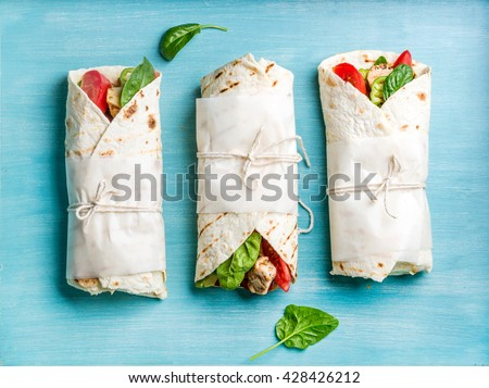 Healthy lunch snack. Tortilla wraps with grilled chicken fillet and fresh vegetables on blue painted wooden background. Top view