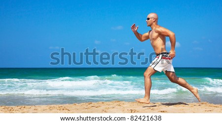 Healthy man running on the beach, doing sport outdoor, freedom, vacation, heath care concept with copy space over natural background