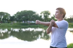 Healthy man stretch exercise beside a lagoon in a morning sunrise to energize and​ refresh before workout run in natural green park. Happy lifestyle. Copy space. Healthcare concept. Selective focus.