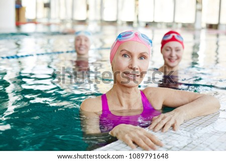 Healthy mature sportswoman and her friends in swimwear spending time in swimming-pool