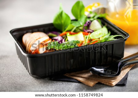 Healthy meal prep containers with  chicken and vegetable salad.