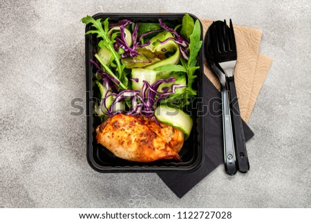 Healthy meal prep containers with  chicken and vegetable salad. Top view