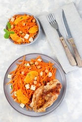 Healthy meal, roasted chicken breast with carrot, chickpeas, feta cheese salad, vertical,   top view