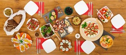 Healthy meals at festive table served for party. Authentic celebration with organic food on wooden table top view. Ratatoille, cheese, corn and chicken barbecue, sandwiches with mojito and lemonade
