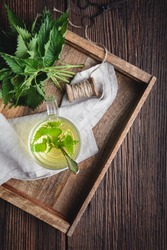 Healthy medicinal drink, nettle tea in a glass cup, decorated with fresh leaves on rustic wooden background