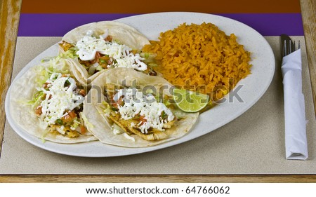 Healthy mexican meal, fish tacos vegetables and rice on plate