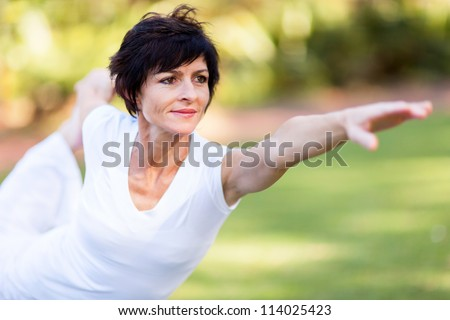 healthy middle aged woman doing fitness stretching outdoors