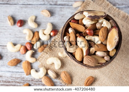 Healthy mix nuts on wooden background. Almonds, hazelnuts, cashews, peanuts, brazilian nuts