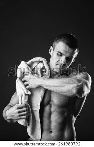 Healthy muscular young man after a workout on dark background.Fitness man holding a orange  towel against dark background.Strong Athletic Man Fitness Model Torso showing  abs. holding towel.