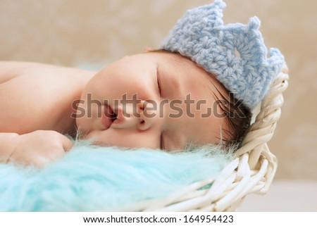 Stock Photo Healthy newborn baby in close up wearing blue knitted prince's crown