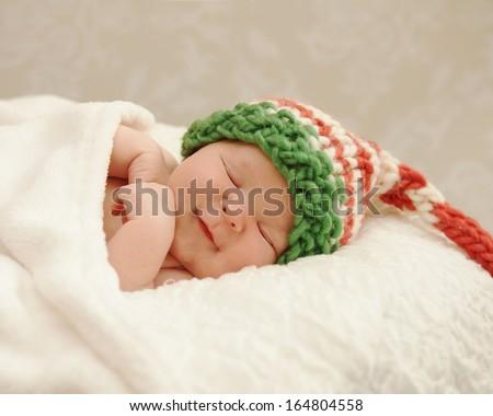 Healthy newborn baby smiling in sleep wearing a Christmas elf hat