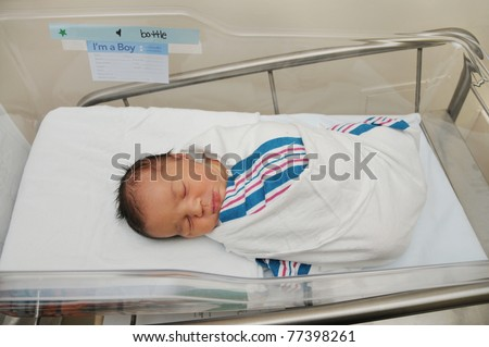 Healthy Newborn Infant Baby Boy Sleeping in Acrylic Hospital Bassinet Wrapped in Pink White Blue Blanket Just after birth