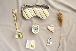 Healthy night sleep concept. Composition with eye sleeping mask, alarm clock, sleep aroma stick that boost relaxation and support the resting phases. Help yourself get to sleep. Flat lay, top view