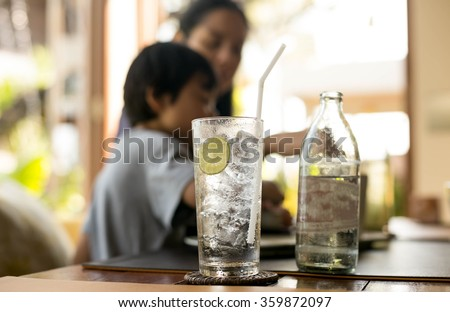 Healthy nutrition of drinking water with lemon and people in blur background