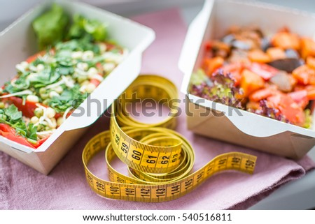 Healthy nutrition plan. Fresh daily meals delivery.  food for weight loss in boxes and a measuring  tape #540516811